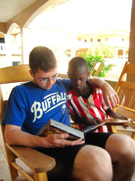 Garvey's son Trent reads to an orphan on a mission trip in Haiti.