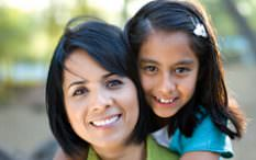 Hispanic mother with daughter on back smiling