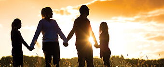 Family in a field holding hands at sunset