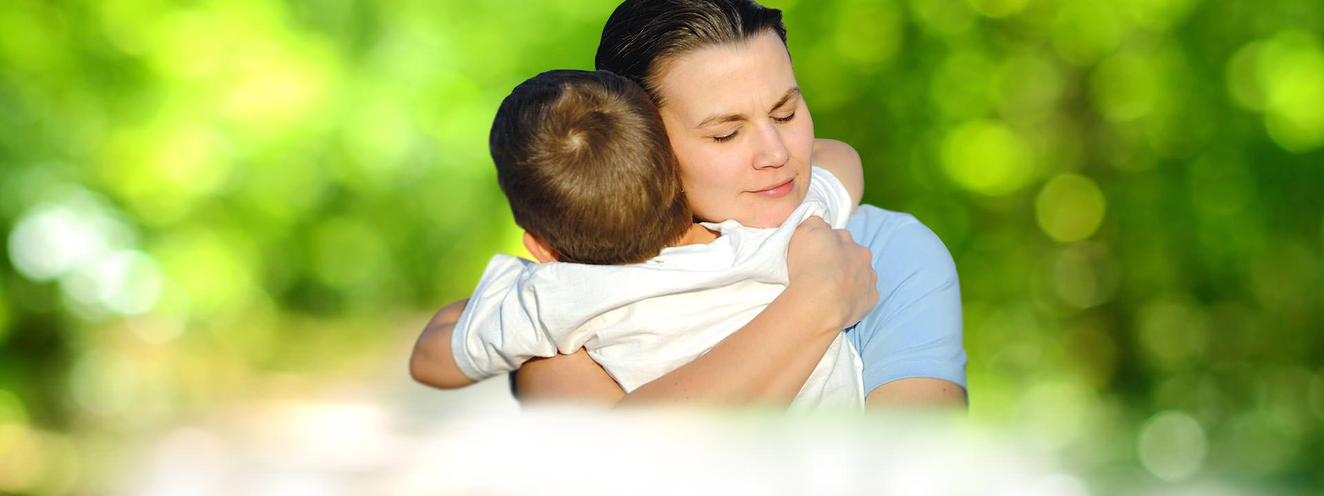 Woman hugging young son blurry green background
