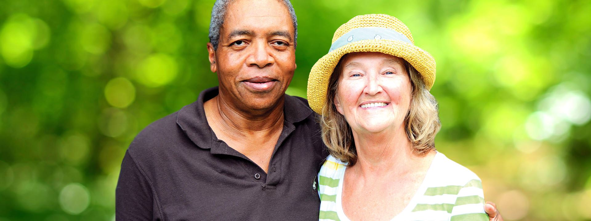 Smiling African American man and white woman blurry green background