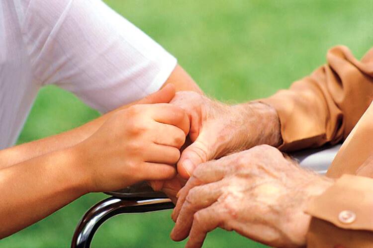 Close up of nurse holding elderly man's hand