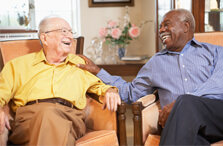Two senior man sitting and laughing