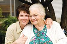 Daughter smiling and hugging elderly mother