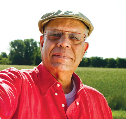 African American male with red glasses and shirt smiling outdoors