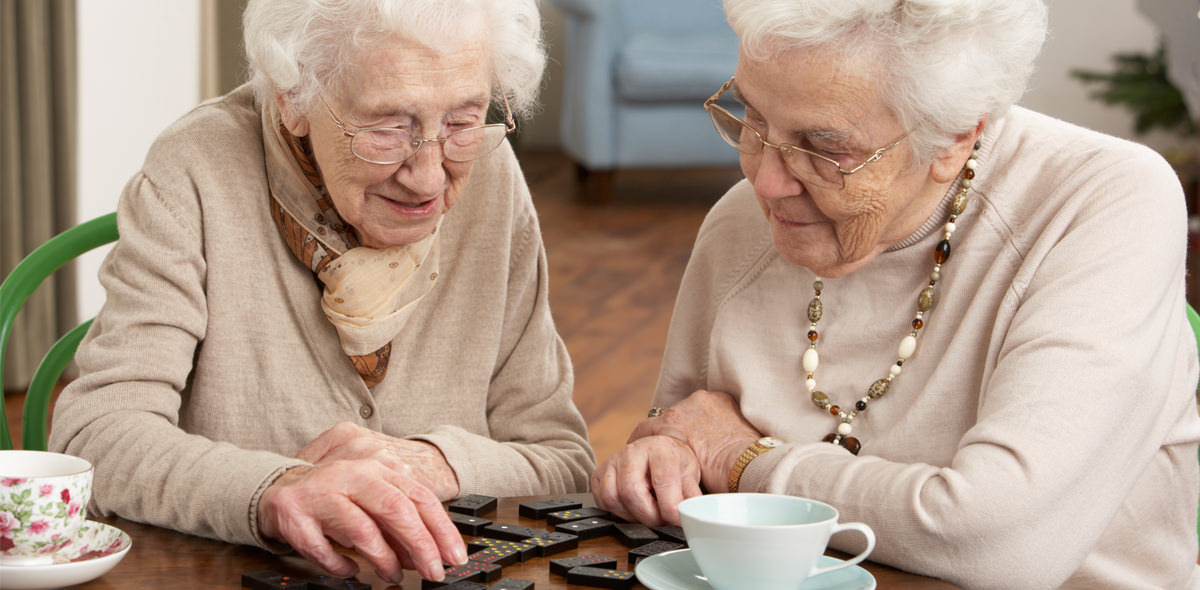 Two elderly women playing dominoes