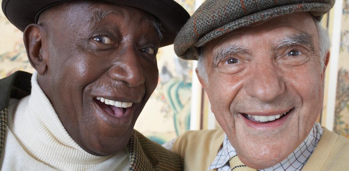 African American and Caucasian Elderly Men Smiling wearing Hats