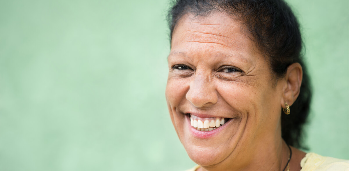 Hispanic woman smiling green background