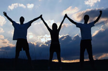 Three people holding hands up at sunset