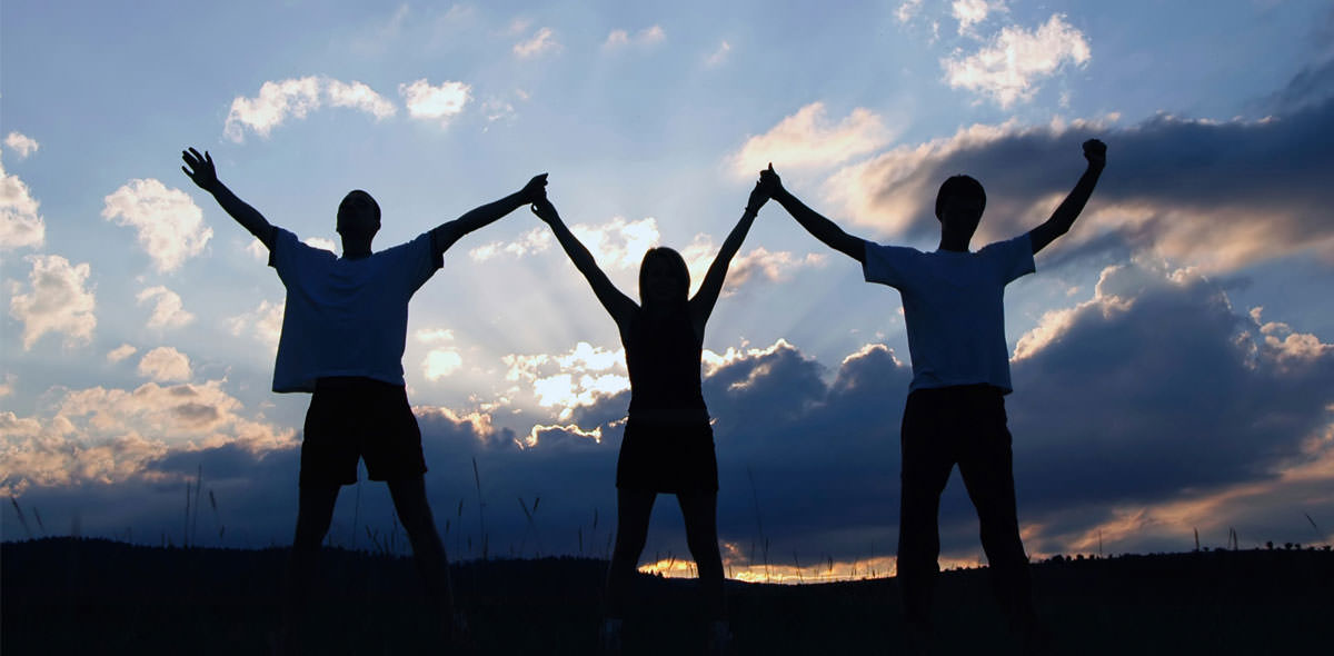 Three People Holding Hands In the Air Sunset