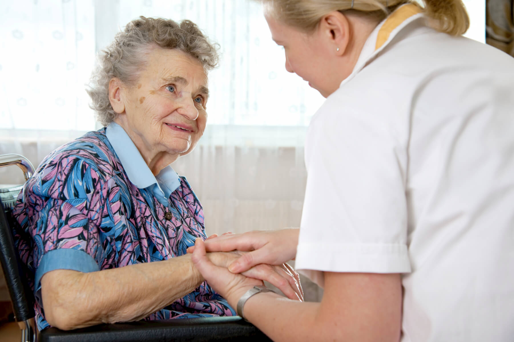 Nurse assisting and holding hand of elderly woman