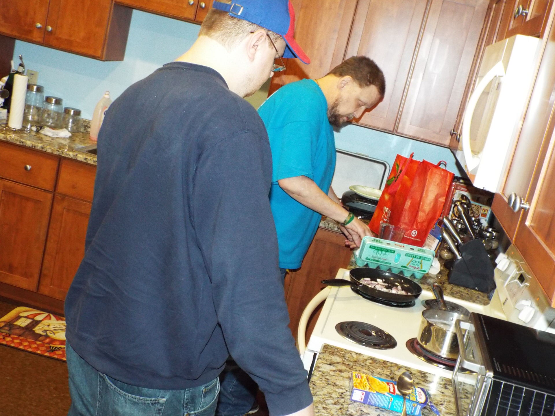 Seneca Square residents Erick K. and Clinton H. prepare food in the community's training kitchen.