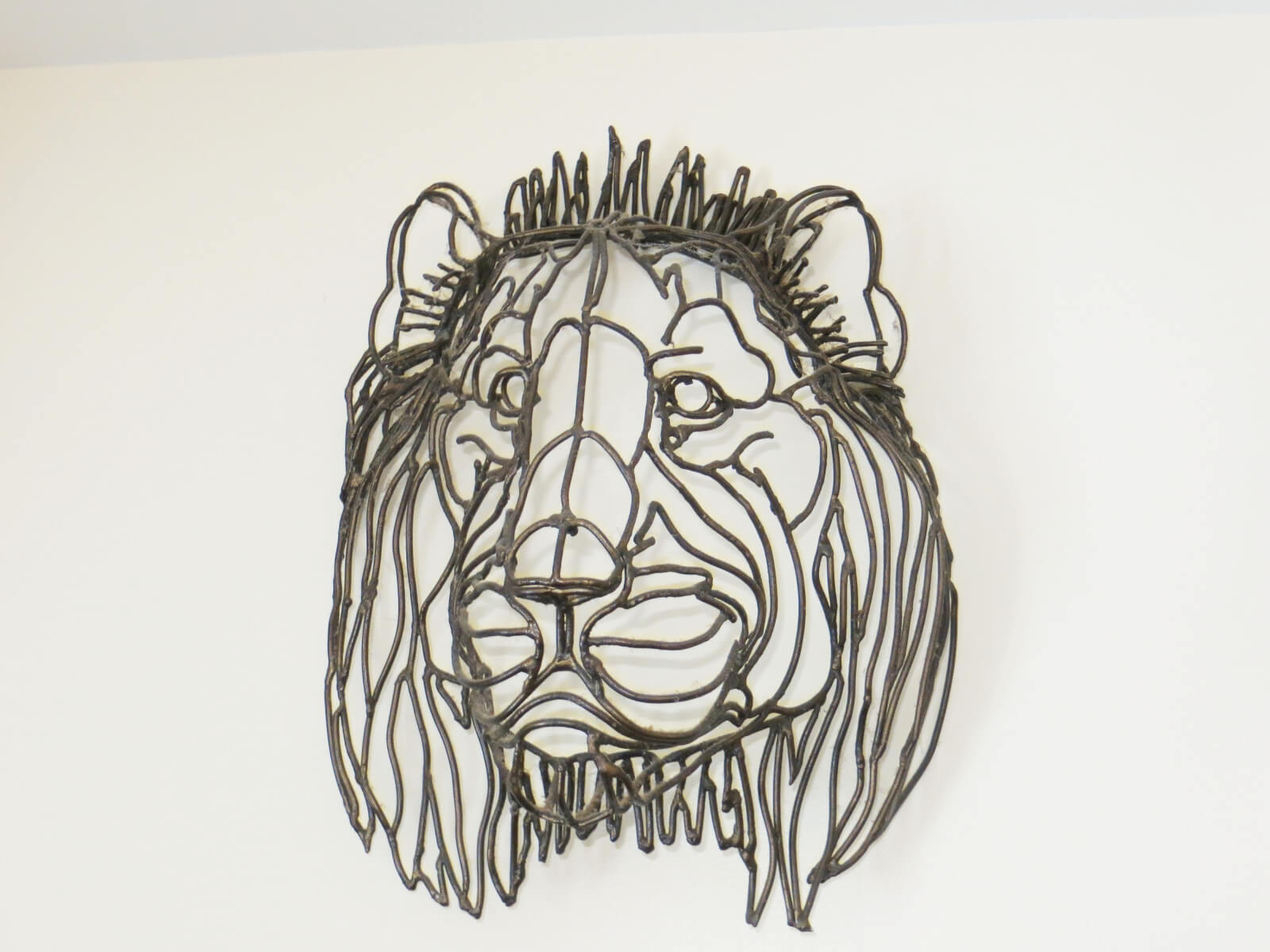 Peter's Metal Lion Head art piece hanging on a wall