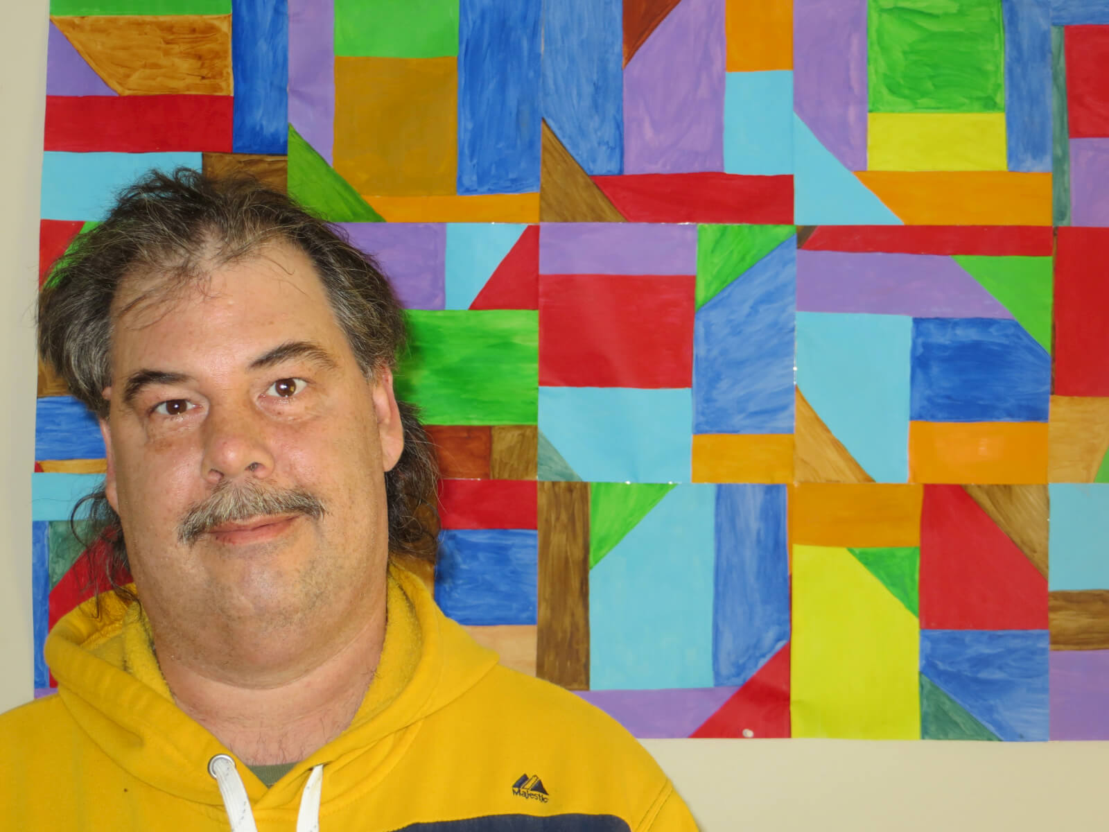 Photo of Peter in front of colorful artwork