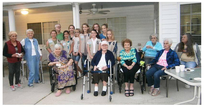 group photo of Girl Scouts and residents celebrating the culmination of the garden project with a pinning ceremony.