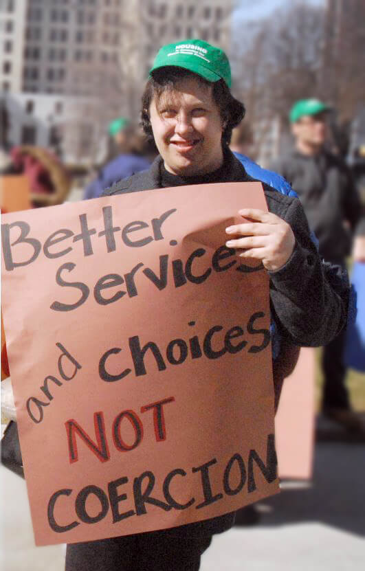 "Photo of DePaul client marching in Albany holding a sign saying ""Better services and choices, not coercion"""